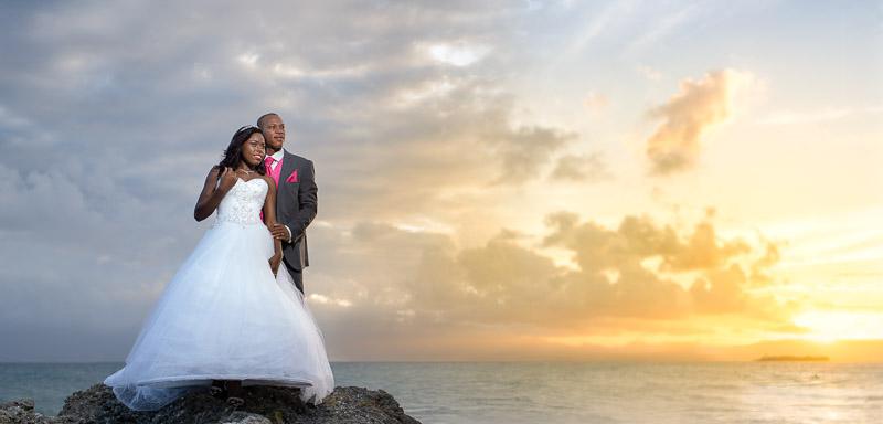 couple de jeunes mariés posent devant le soleil couchant à la plage de Saint-Félix, Le Gosier, Guadeloupe